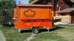Foodtruck de 3 metros de largo, color naranjo portalones cerrados.